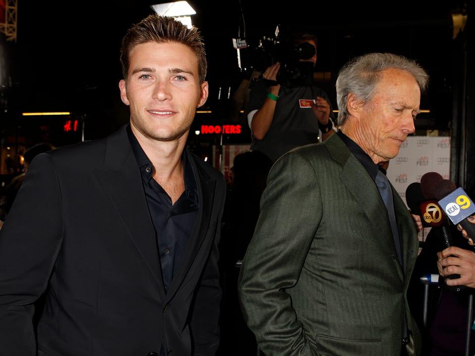 Scott Eastwood für die Kamera posierend, Clint Eastwood gibt im Hintergrund ein Interview.
