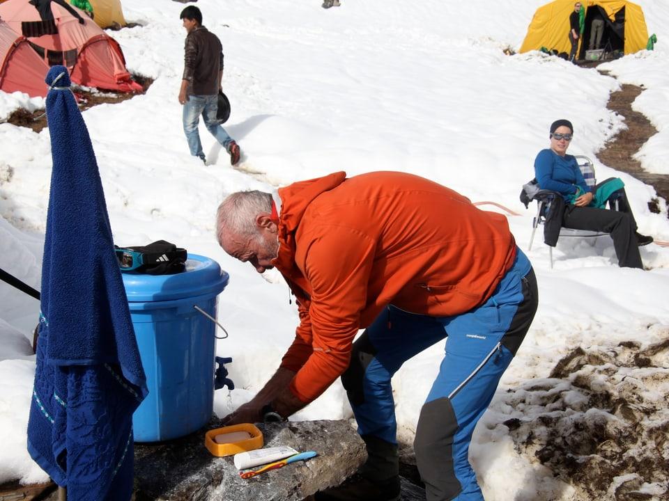 Wasserstelle im Basislager. Ein Teilnehmer versucht sich zu waschen.
