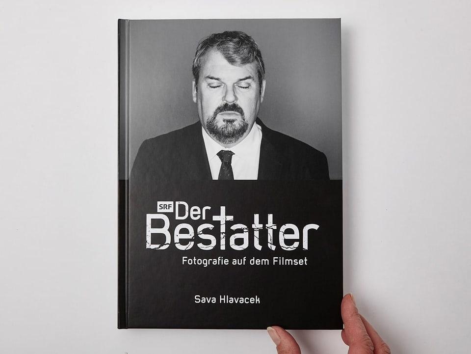 Hand hält das Fotobuch der Bestatter mit Bildern von allen 7 Bestatter Staffeln