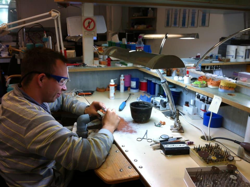 Zahntechniker mit Schutzbrille arbeitetet an einem Gebiss.