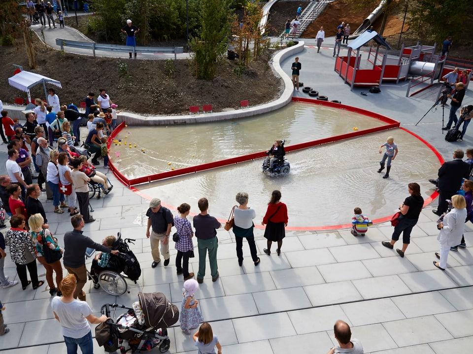 Menschen in einem Park mit Wasserfläche.