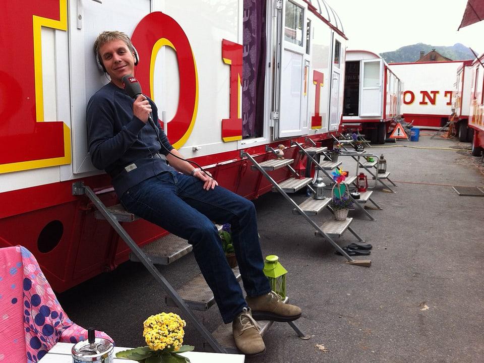 Reto Scherrer sitzt vor Zirkuswagen.