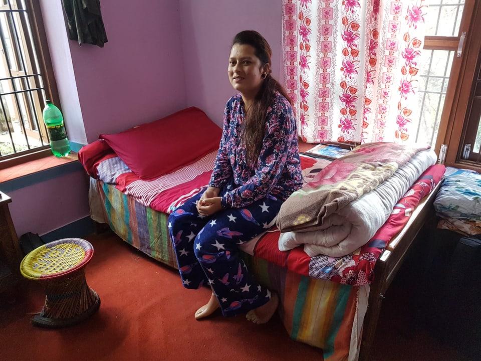 Das Bild zeigt eine Frau auf einem Bett.