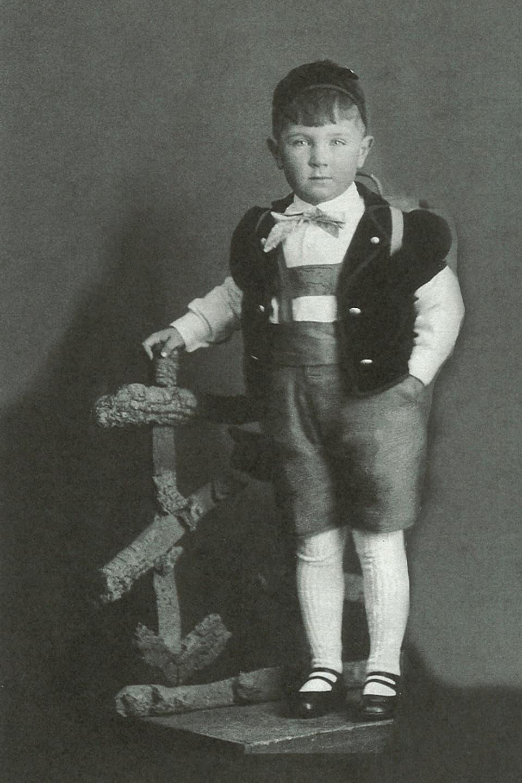 Sepp Renggli mit etwa sechs Jahren. Er steht auf einem Hocker und blickt etwas ernst in die Kamera.