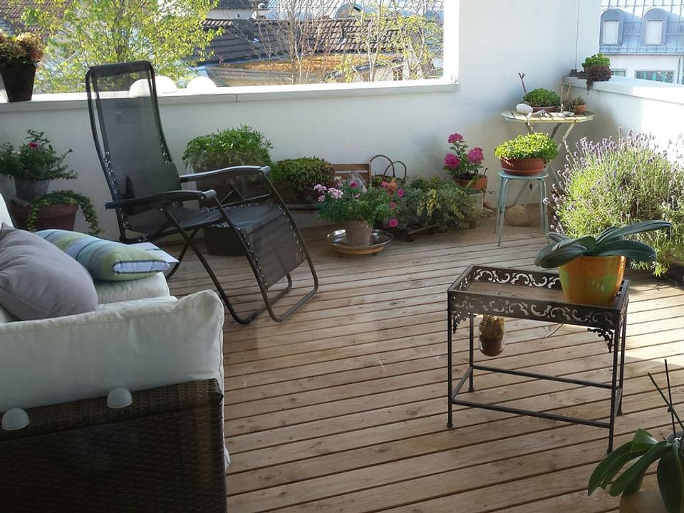 Balkon mit Holzboden, Sofa und schön assortierten Topfpflanzen.