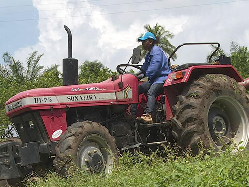 Die Lernende auf dem roten Traktor während der Feldarbeit.
