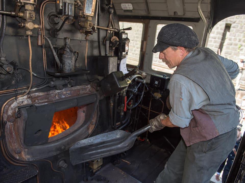 Ein Mann schaufelt Kohle in einem Führerstand
