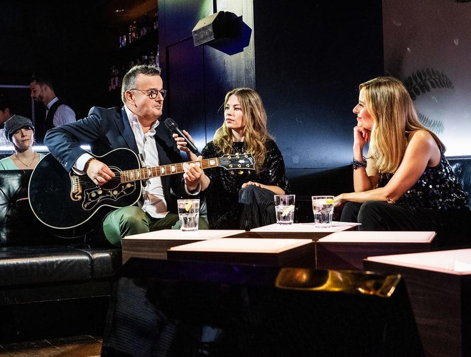 Ein Mann mit Gitarre und zwei Frauen sitzen auf einem Sofa