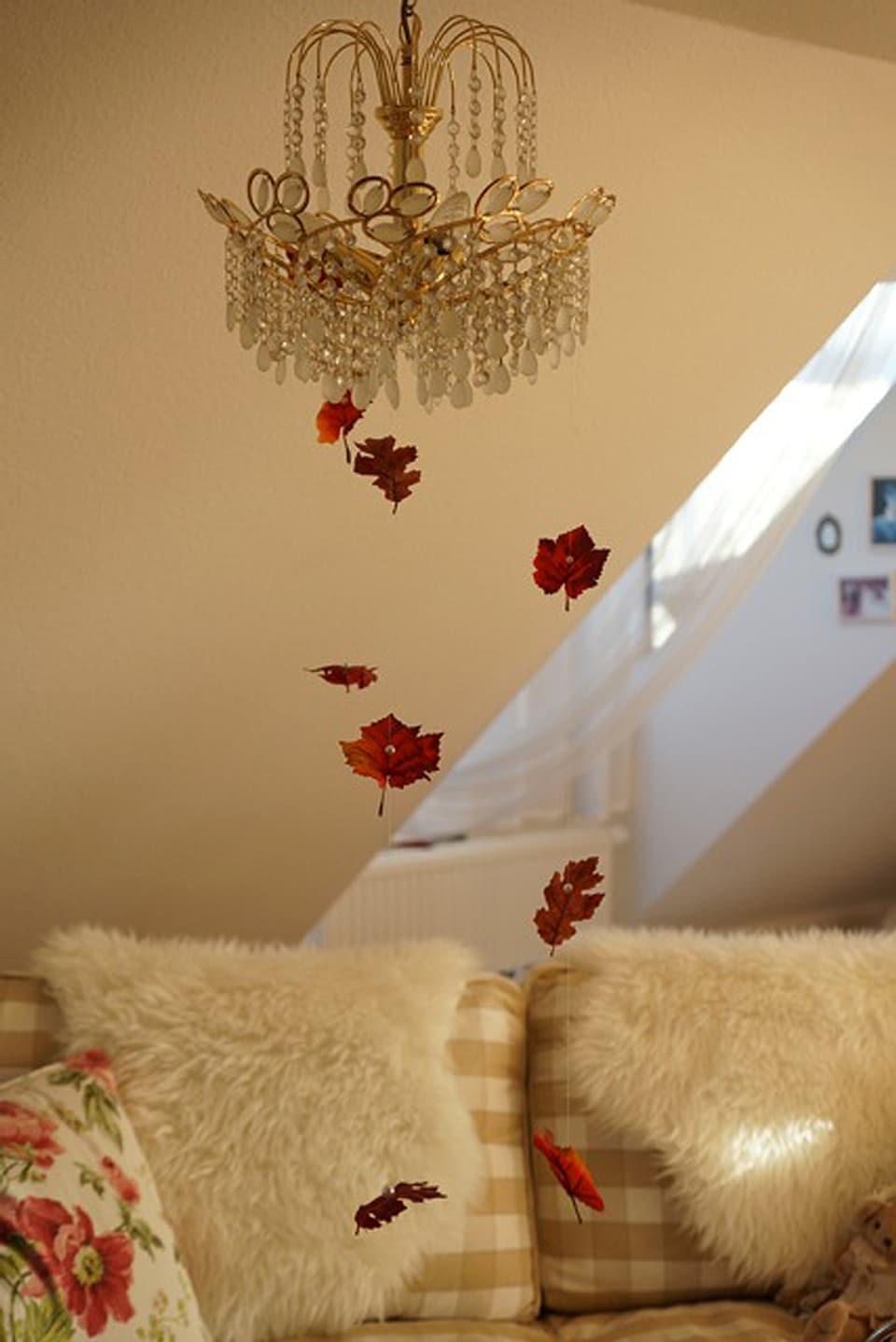 Farbige Herbstblätter schweben im Raum. Sie wurden auf einen Nylonfaden aufgezogen.