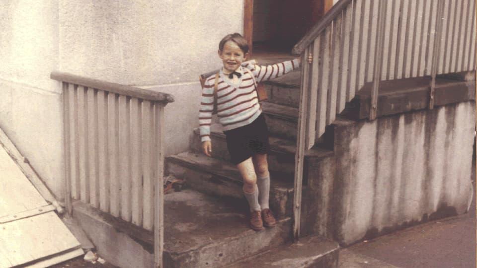 Hermann steht auf der Treppe und hält sich am Geländer fest.