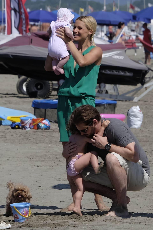 Michelle Hunziker hält ein Baby hoch. Tomaso Trussardi kniet auf dem Sand und ein kleines Mädchen krabbelt auf seine Knie.