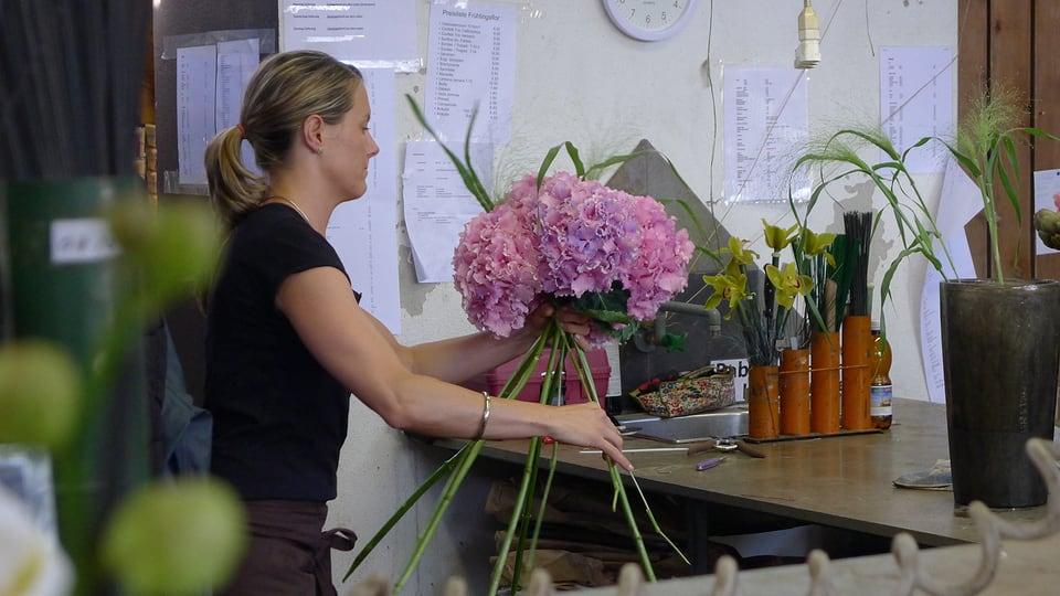 Eine Floristin gestaltet einen runden Strauss aus lila Hortensien.