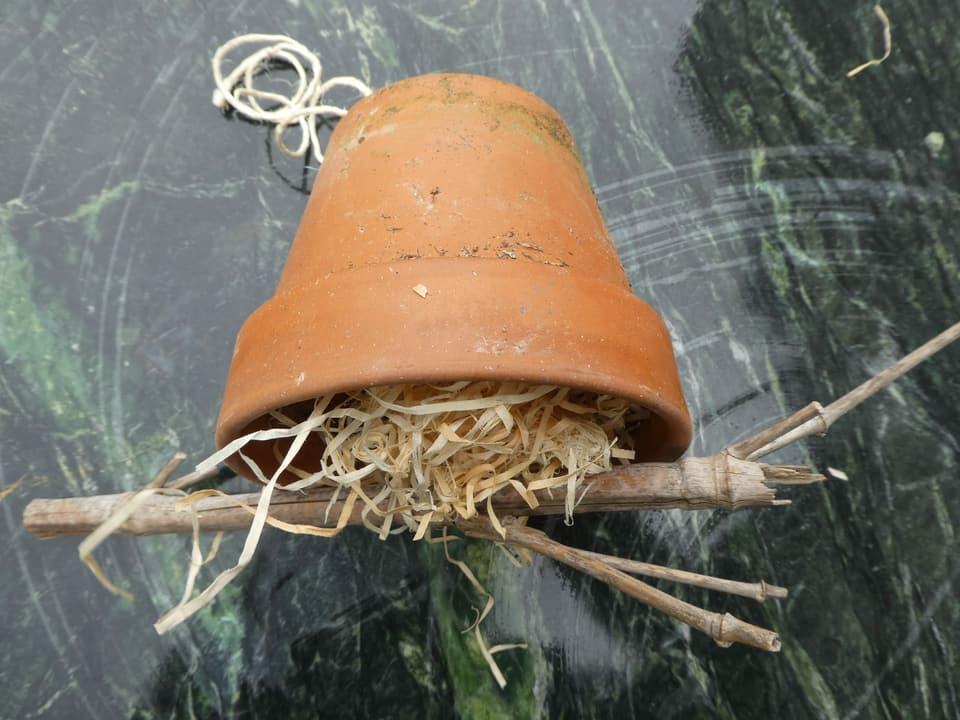 Ein Tontopf ist mit Holzwolle gefüllt. Darüber ein Ast-Teil, der mit einer Schnur angebunden ist.