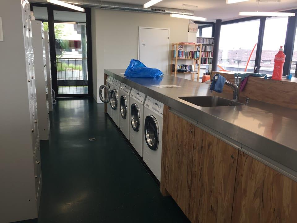 Fünf Waschmaschinen in einem Waschsalon.