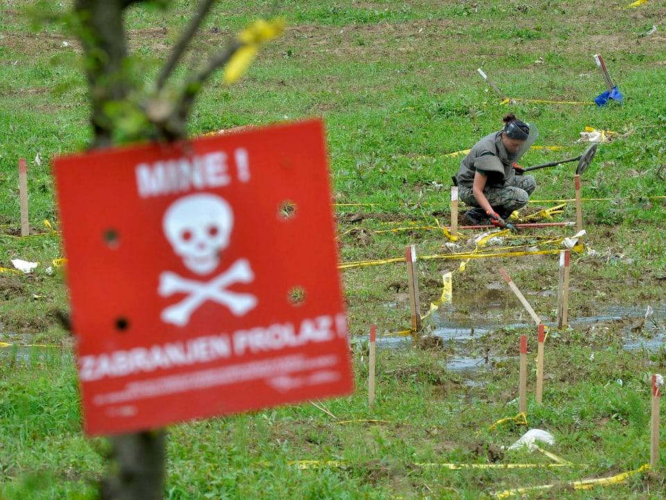 Eine Soldatin sucht ein abgestecktes Gebiet nach Minen ab.