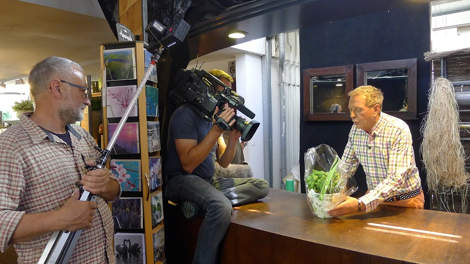Kurt Aeschbacher stellt einen Topf mit Basilikum hin. Kameramann Jörg Glaser sitzt auf dem Tisch und filmt von oben, während Andreas Hagen die Szene ausleuchtet.