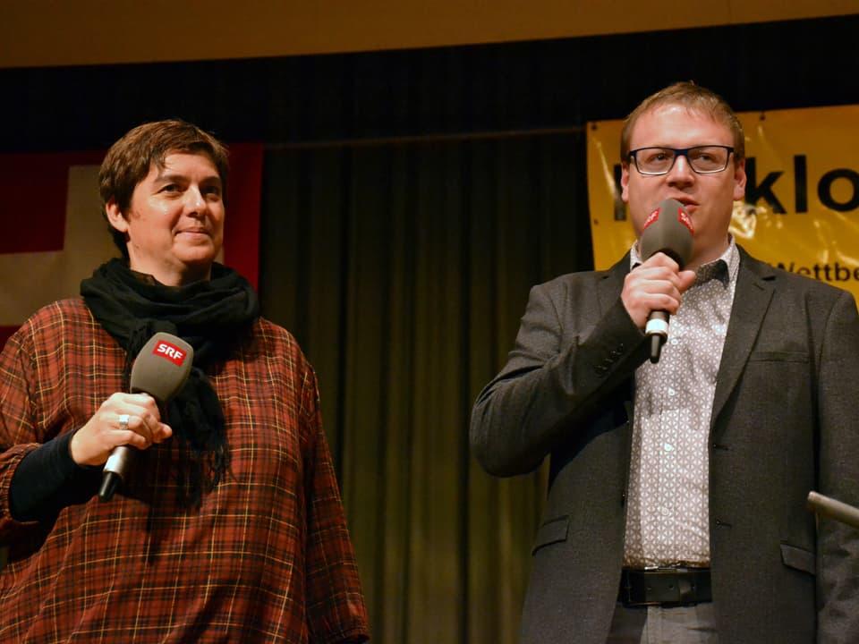 Moderatorin und Moderator mit Mikrofonen auf der Bühne.