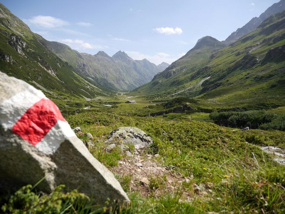 Ein grosser Stein mit der Markierung für Wanderwege im Val Bever.