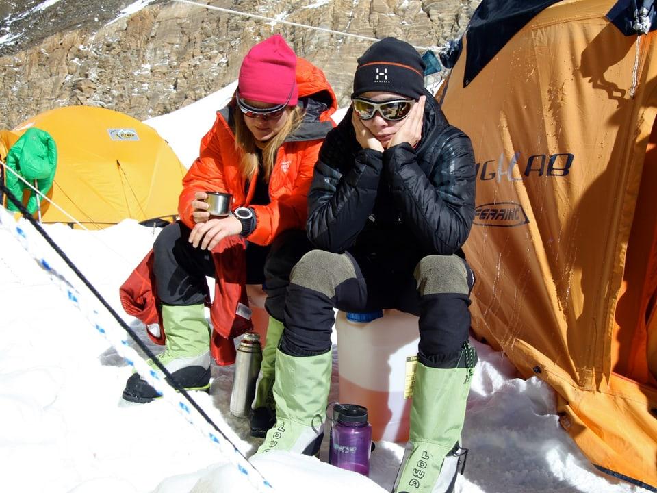 Zwei Expeditionsteilnehmerinnen sitzen vor dem Zelt.