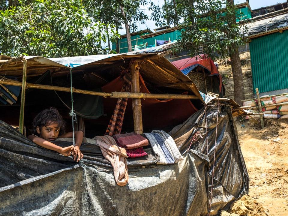 Ein Kind schaut aus einer einfachen Hütte.