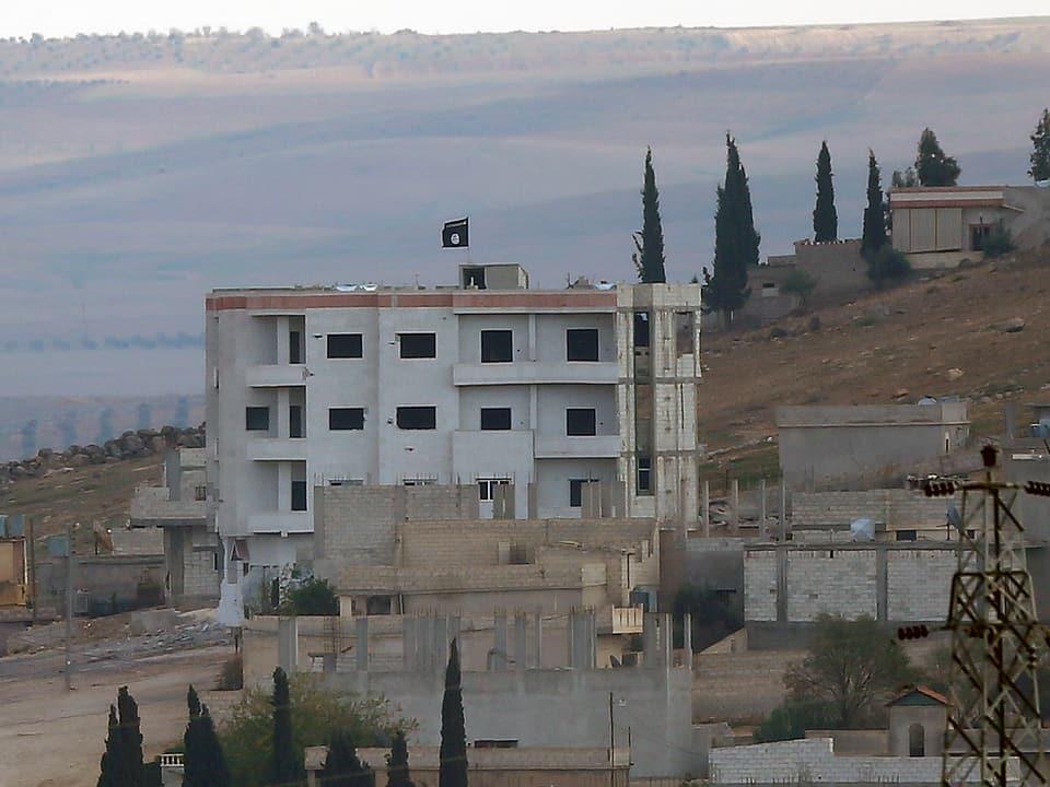 Wohnhaus im belagerten Kobane mit IS-Flagge