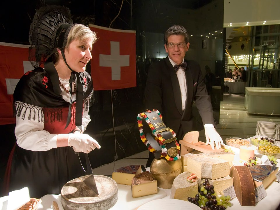 Babara John in Sonntagstracht und ihr Ehemann hinter dem Käsebuffett mit vielen verschiedenen Käsesorten.