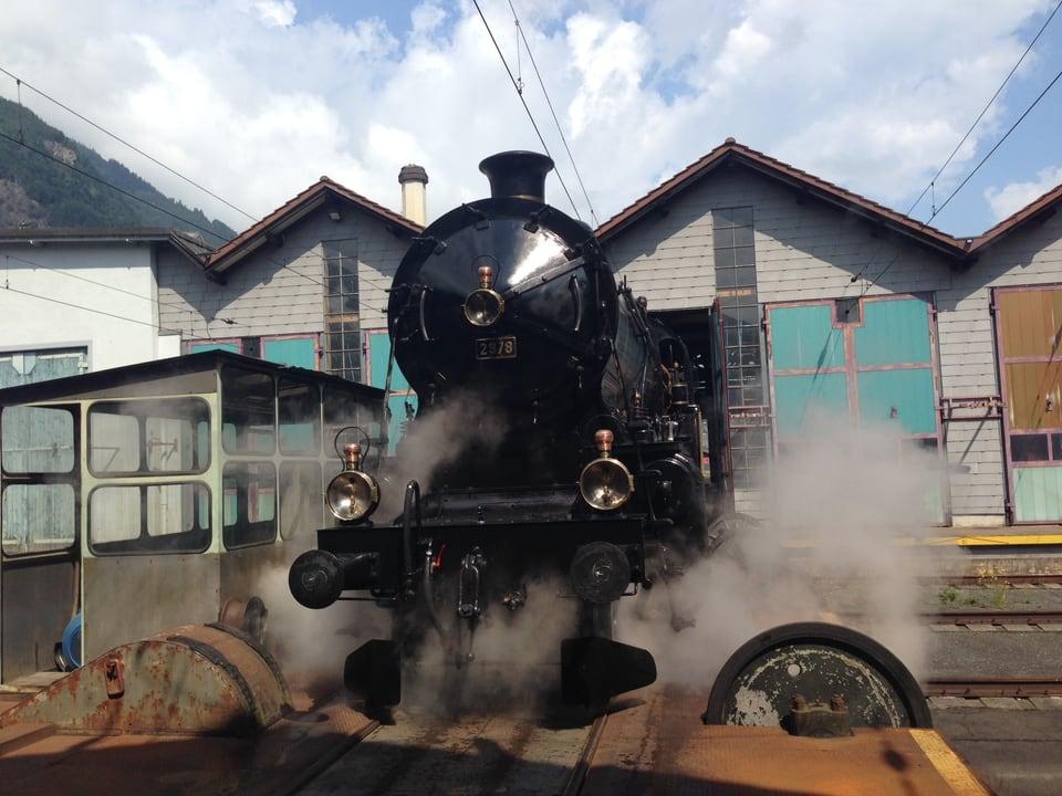 Schwarze Lokomotive steht vor einem Zugsdepot, rundherum dampft es
