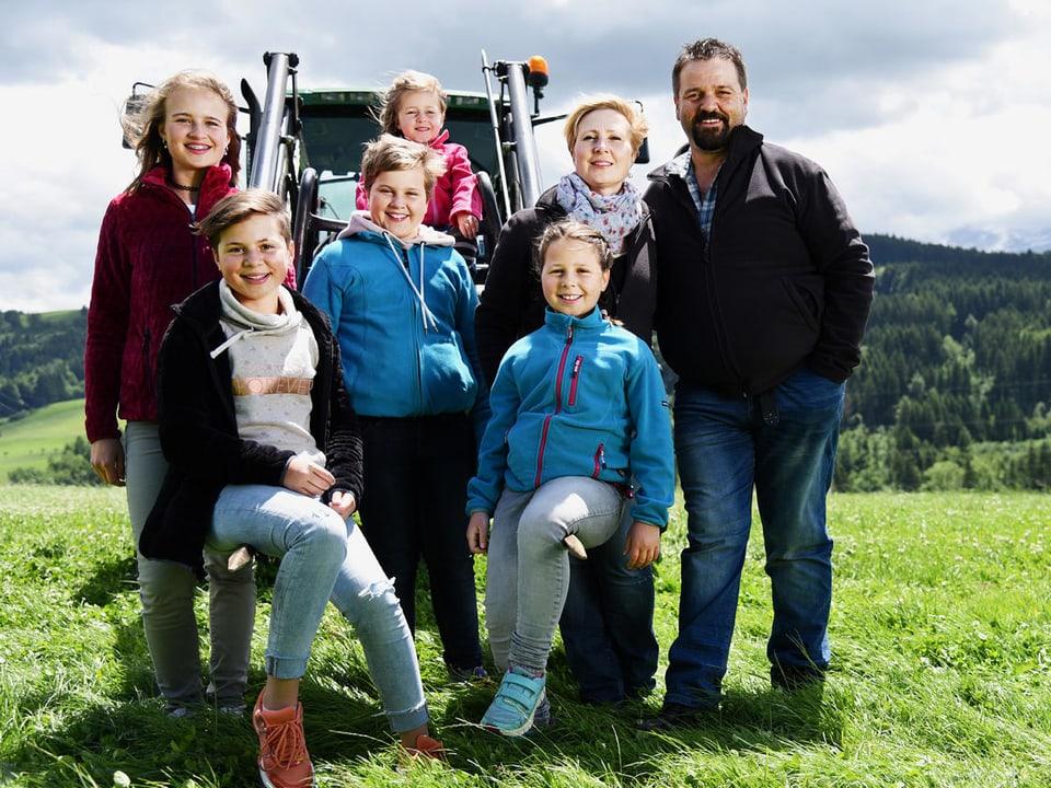 Familie vor Traktor.