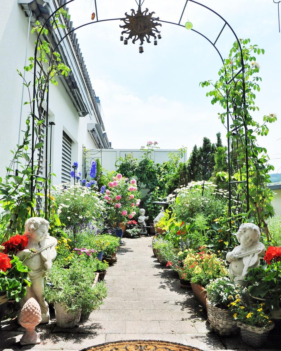 Balkon mit Stein-Engeln und vielen Pflanzen.