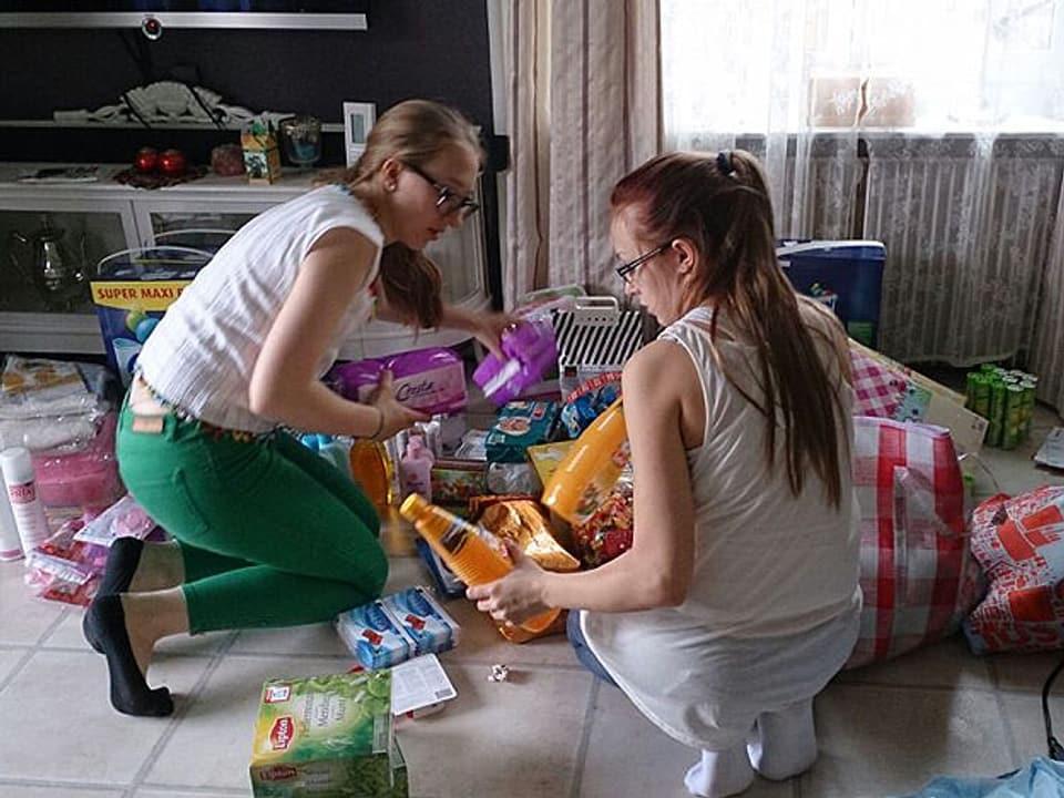 Zwei Mädchen packen Alltagsgegenstände zusammen.