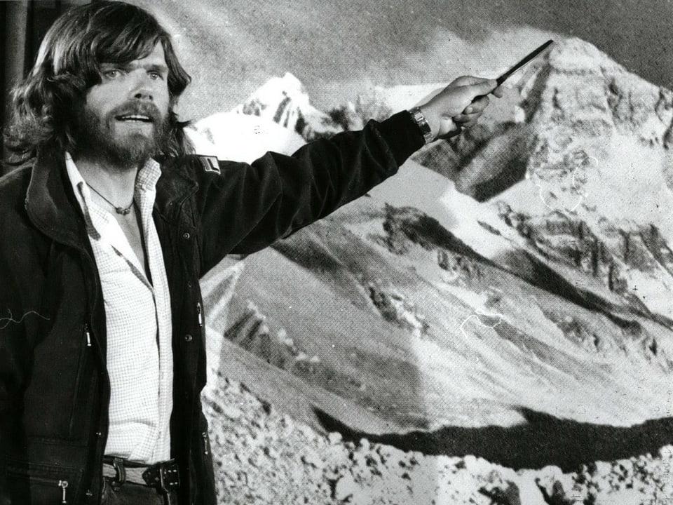 Schwarzweissaufnahme von Messner, der auf den Gipfel eines Bergs zeigt.