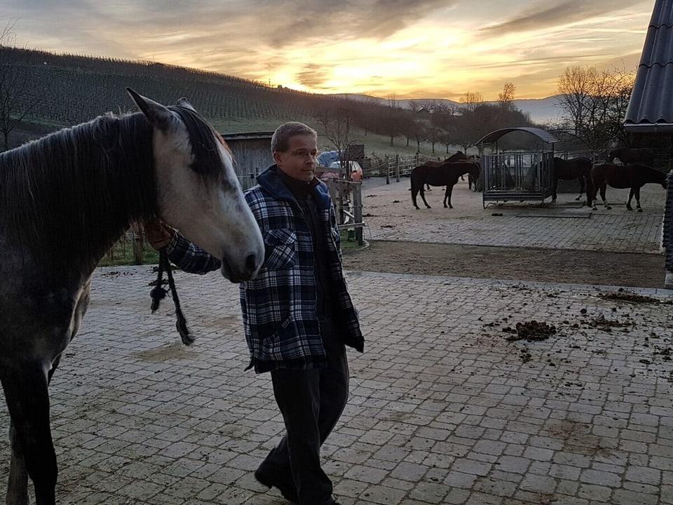 Mann führt ein Pferd bei Morgendämmerung.