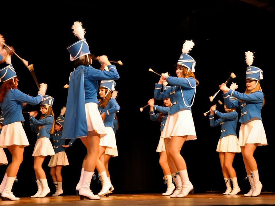 Majoretten in weissen Röcken und blauen Jacken schwungvoll auf der Bühne.