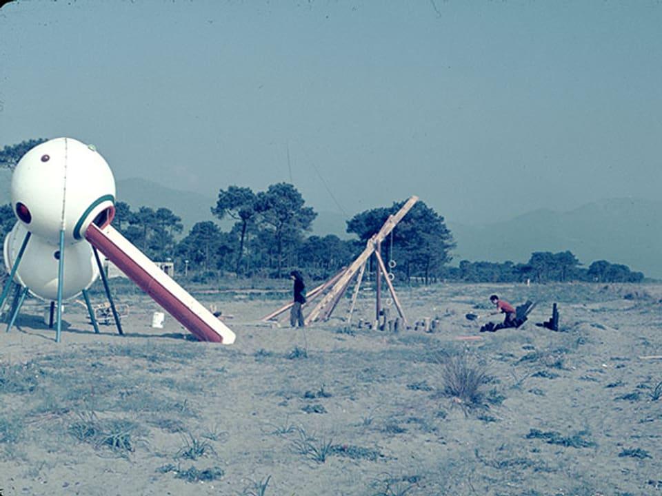 Spielplatz mit weissen Elementen in karger Landschaft.