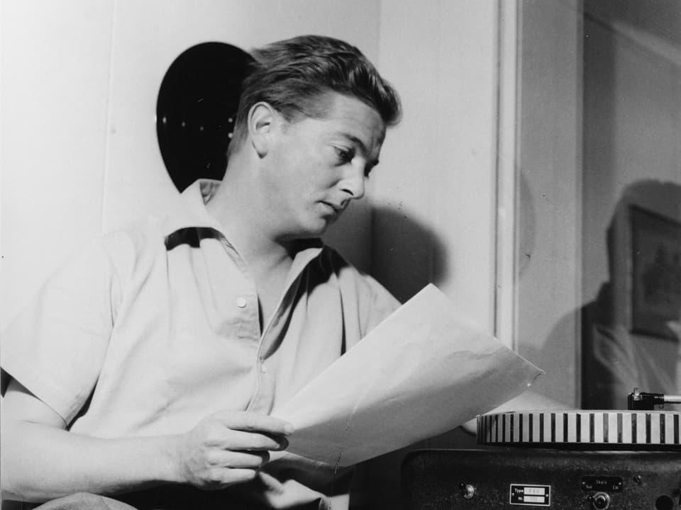Sepp Renggli mit Manuskript vor einem Plattenspieler.