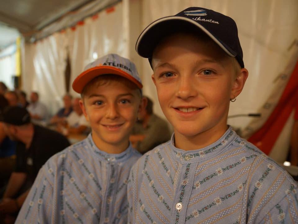 Zwei blonde Jungs im «Sennenchutteli» mit Baseballmütze.