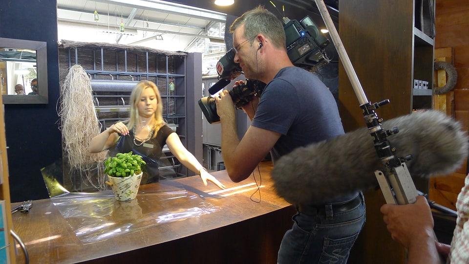 Der Kameramann filmt die Floristin, die den Topf mit Basilikum in Folie einpackt. Im Vordergrund ist der Windschutz des Mikrofons zu sehen, der das beim Einpacken entstehende Geräusch tonmässig aufnimmt.