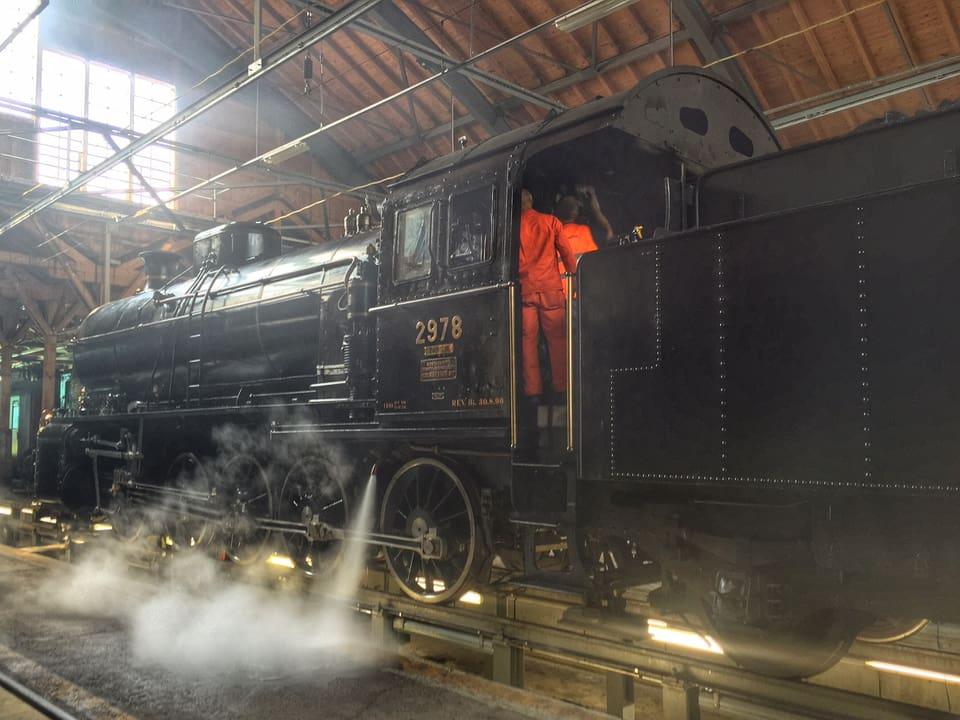 Dampflok steht in einem Depot, zwei Männer in orangen Anzügen führen Kontrollarbeiten durch
