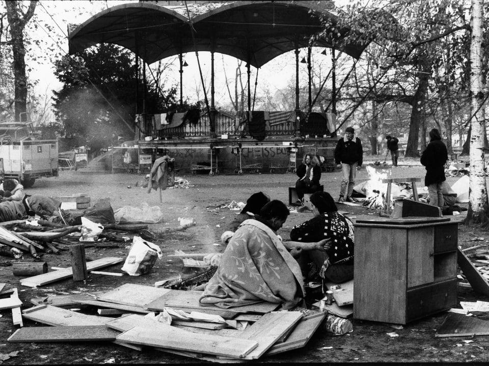 Schwarzweiss Fotografie, Drogensüchtige am Boden und auf Kartonschachteln im Park.