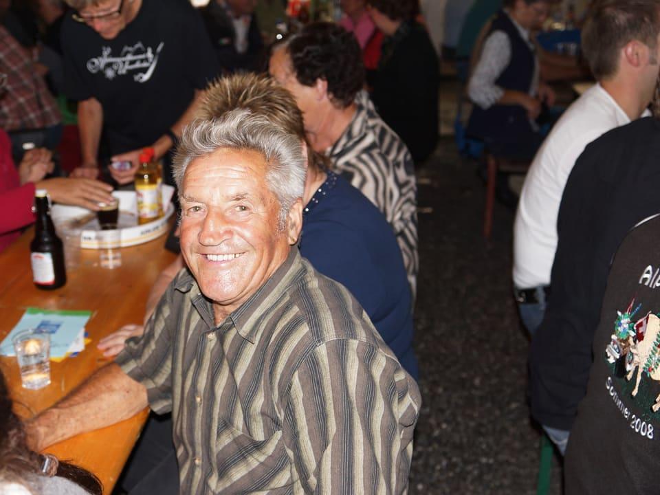 Ein älterer Mann mit grauen Haaren und gestreiftem Hemd blickt in die Kamera.