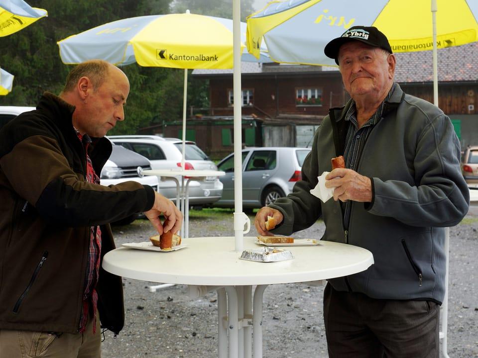 Zwei Männer verzehren an einem Stehtisch eine Wurst.