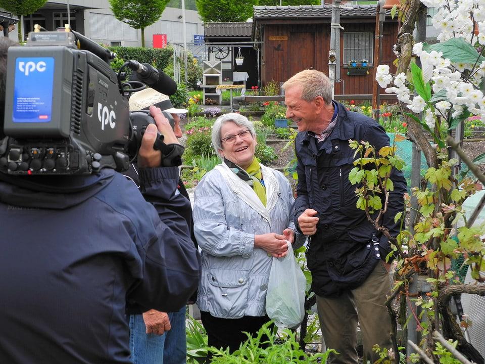 Ueli Haberstich filmt Silvia Di Cesare und Kurt Aeschbacher (verdeckt Francesco Di Cesare). Sie befinden sich auf dem Pflanzblätz, Silvia trägt einen Plastiksack mit geerntetem Salat.