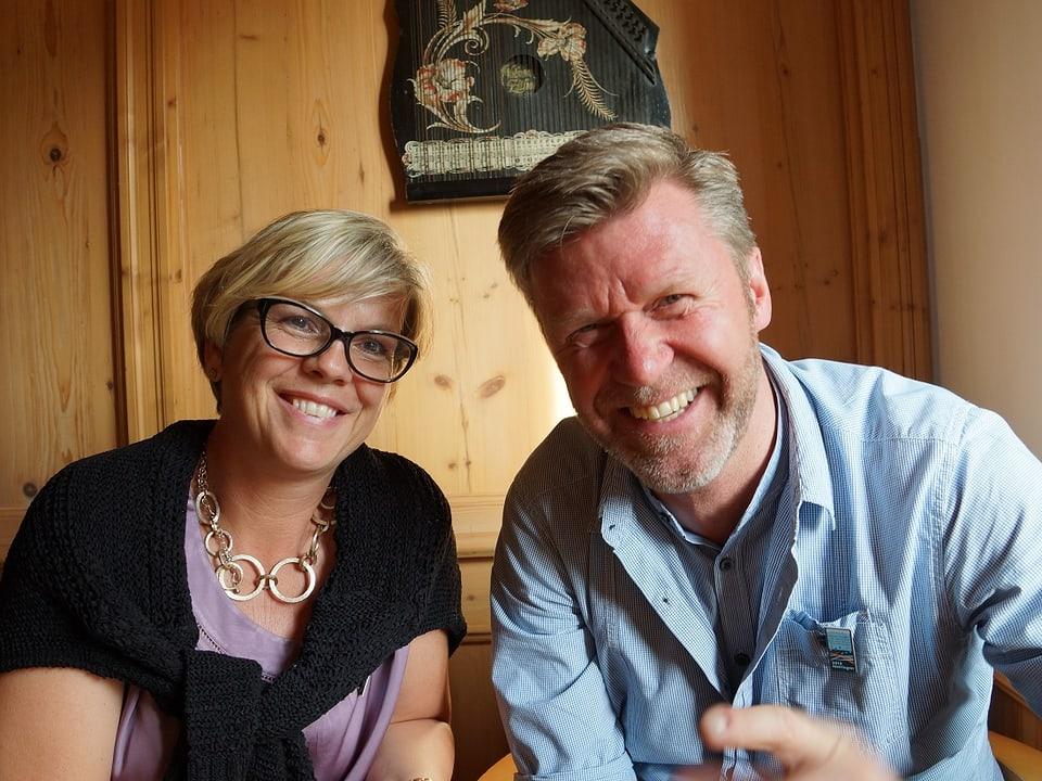 Das Paar sitzt nebeneinder am Tisch in einer Gaststube und lacht in die Kamera.