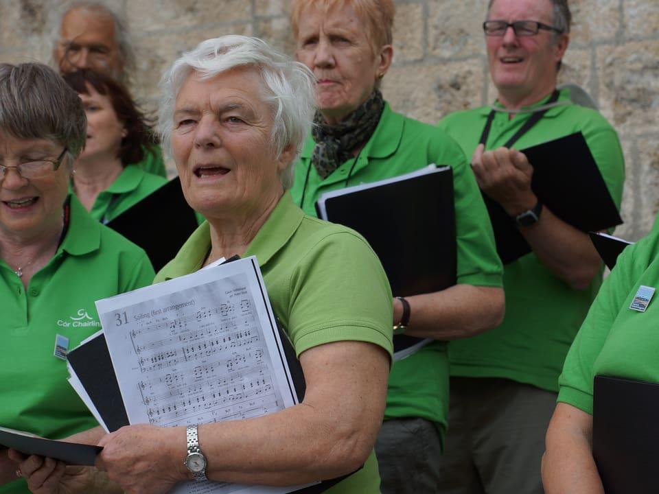 Chorsängerinnen und -sänger in hellgrünen Polo-Shirts und mit Notenblättern in den Händen.