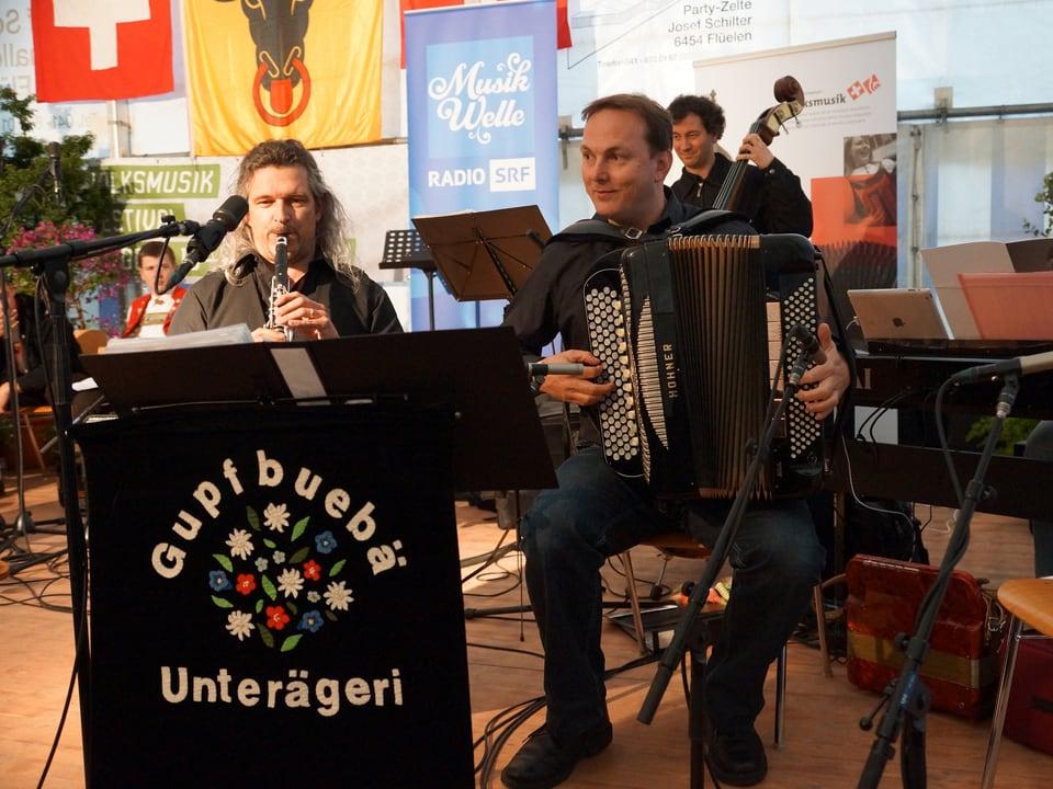Drei Musikanten mit Klarinette, Akkordeon und Kontrabass.
