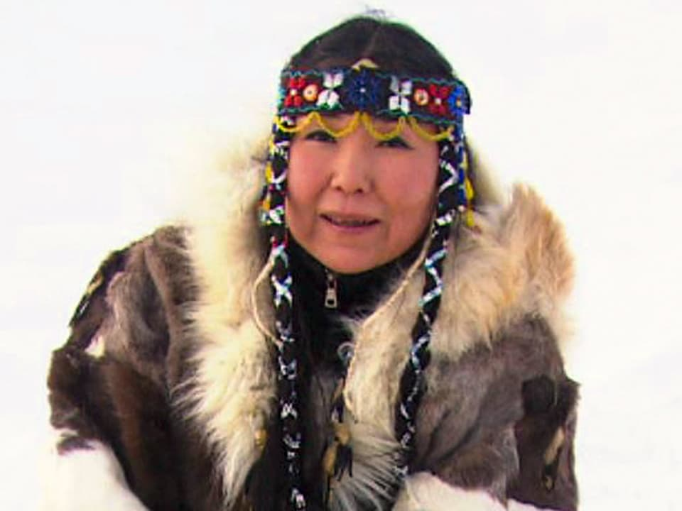 Singen im Wind: Chukchi-Frau Olga in traditioneller Kleidung der sibirischen Schamaninnen beschwört Tiergeister (Porträtfoto)