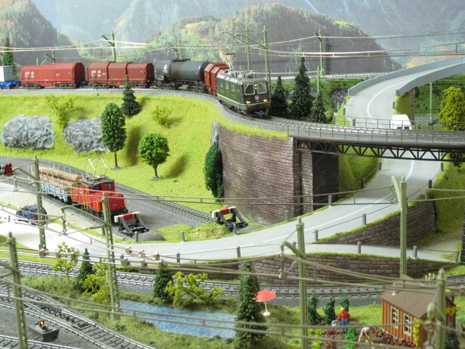 Modelleisenbahn: Zugbrücke führt über Strasse.