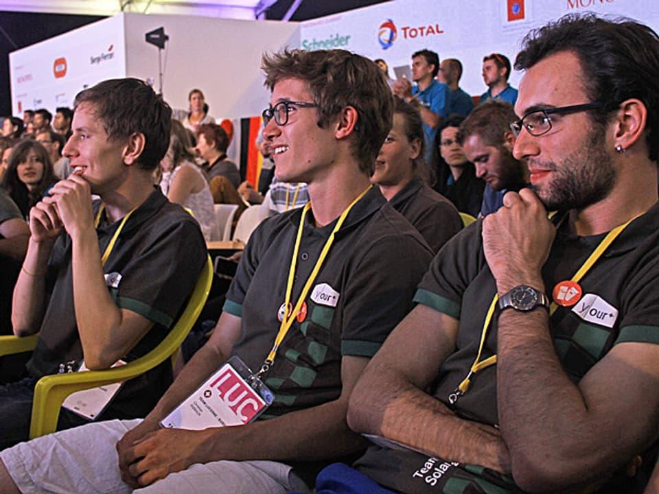 Drei Schweizer Projektmitarbeiter in den Zuschauerrängen.