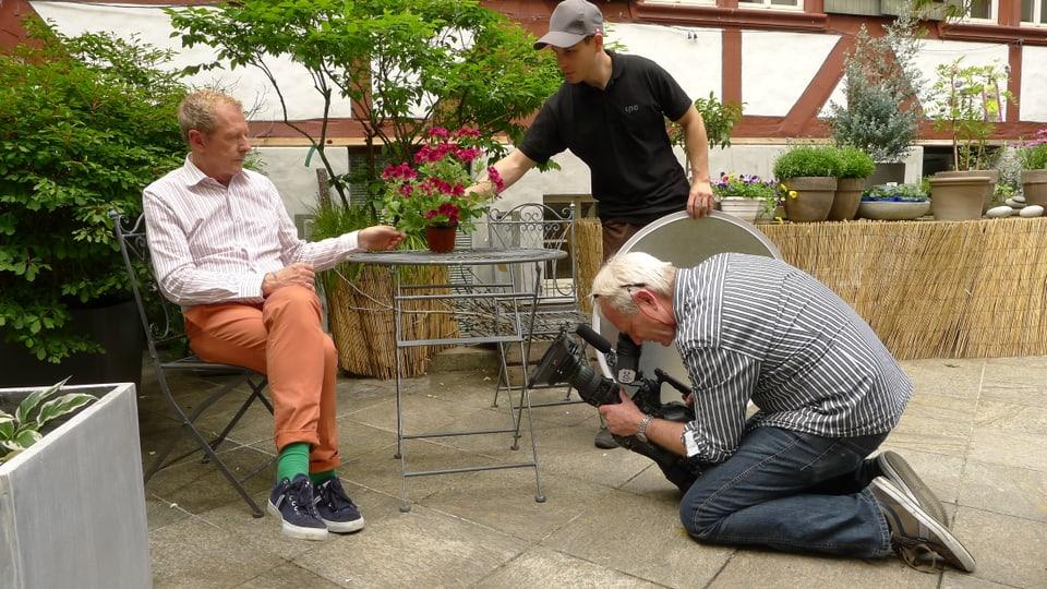 Kurt Aeschbacher sitzt draussen an einem Eisentischchen. Der Beleuchter David Frauenknecht richtet den Topf roter Blüten, während der Kameramann am Boden kniend die Szene filmt.