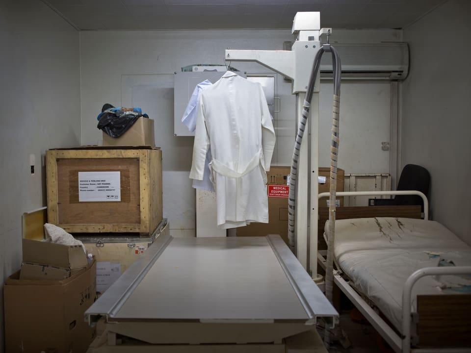 Fensterloser Lagerraum mit Kisten, einem Metallbett und einem Röntengerät an dem ein weisser Kittel hängt.
